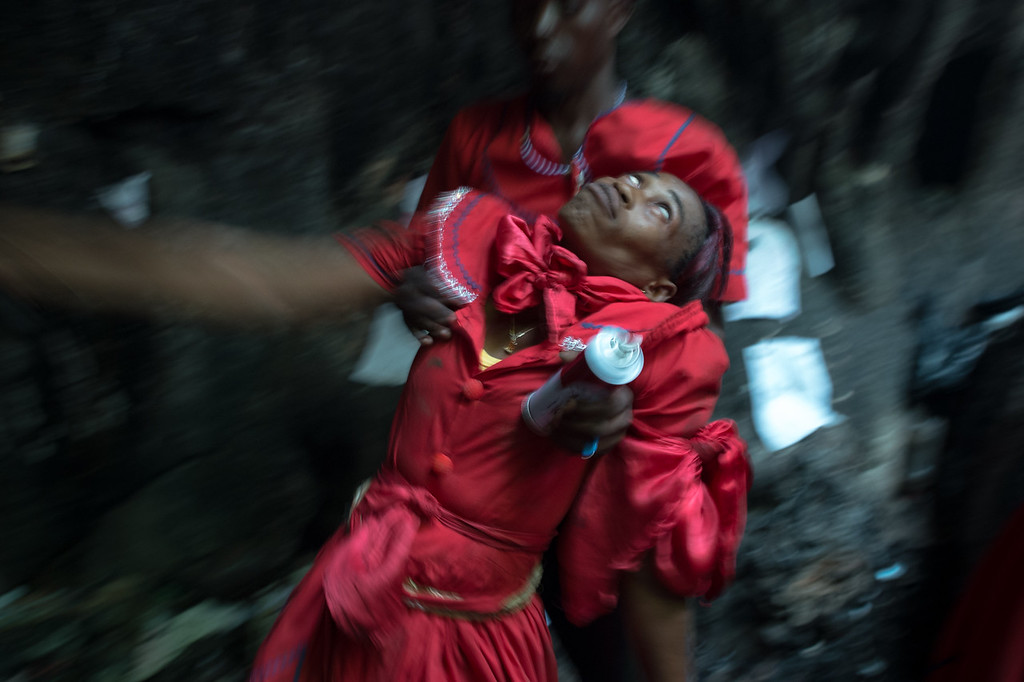 A  mambo (Vodou priestess) is overcome by an Iwa (spiritual entity) as she enters a trance like state.