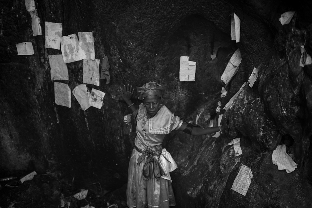 A Mambo deep in prayer along a cavern wall covered with written requests from previous worshipers.
