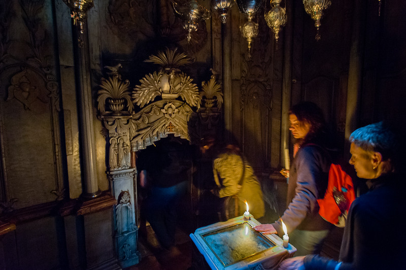 Jerusalem. Pilgrims touch the Angel's Stone (a fragment of the stone believed to have sealed the tomb after Jesus' burial) before entering the first of the two chambers of the Edicule, the second one being the tomb itself.