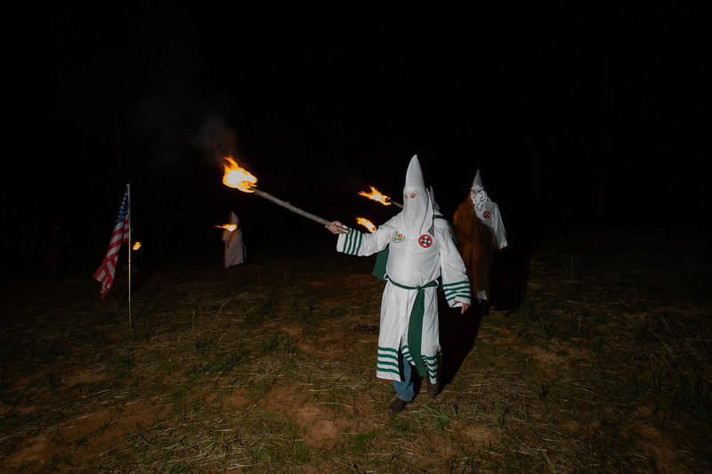 Klan members participating in a  Cross lighting ceremony form a circle with torches as they prepare to ignite the base of an 18-foot wooded cross, wrapped in burlap and soaked with kerosene.<br /> <br /> According to Klan beliefs, the light of the cross symbolizes the light of Christ dispelling darkness and ignorance. The Klan adopted the fiery cross from the traditions of old Scotland where the fiery cross was used as a symbol against tyranny and for the fight for freedom.