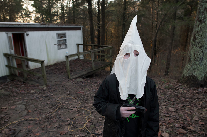 A young boy holding an Airsoft pistol while wearing his father's Klan helmet.