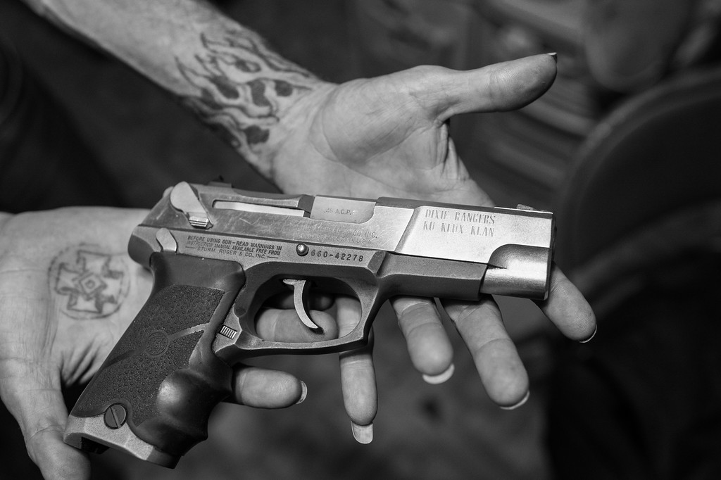 "A former Imperial Officer of the since disbanded Dixie Rangers of the Ku Klux Klan shows off his engraved .45 cal Ruger pistol. The tattoo on his right palm is a ""Mioak."" ""Mioak"" stands for: The Mystic Insignia of a Klansman. Today it is most commonly known as the Blood Drop Cross. It is displayed as the patch seen on the robes of Klansmen. It is also a part of the Imperial Seal of the Klan."