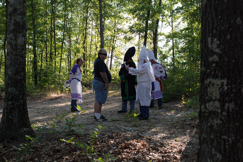 "Candidates wishing to become citizens of the Ku Klux Klan take part in a Naturalization ceremony. There are some parts of the ceremony that many might at first mistake for a ""hazing"". Proposed Klansmen are blindfolded, and then with one arm placed on the shoulder of the man before him, led through the woods at a sometimes-vigorous pace. The link is not to be broken as they are questioned on Klan history and intimidated occasionally with the sound of a firearm. According to Klan beliefs, the ""hazing"" actually has symbolic purpose, and builds mutual trust, loyalty and reveals personal bravery and dedication. Missouri."