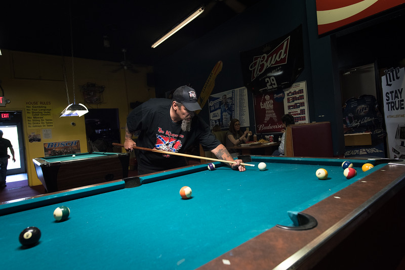 In a bar known for its support of the white power movement, a local Klansman plays a solo game of pool.