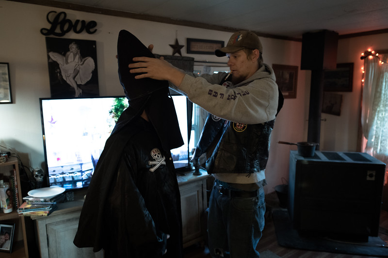 "11/24/2018. Kentucky. USA. A Klansman helps a fellow Klansman adjust his ""helmet"" prior to a cross lighting ceremony. The black robe is worn by the Imperial Knighthawk, a security/courier position within the Klan"
