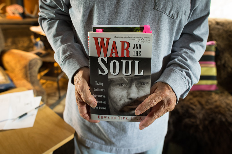 Basil Brave Heart, a member of the Oglala Sioux Tribe and a Korean War veteran holds a copy of War and the Soul.