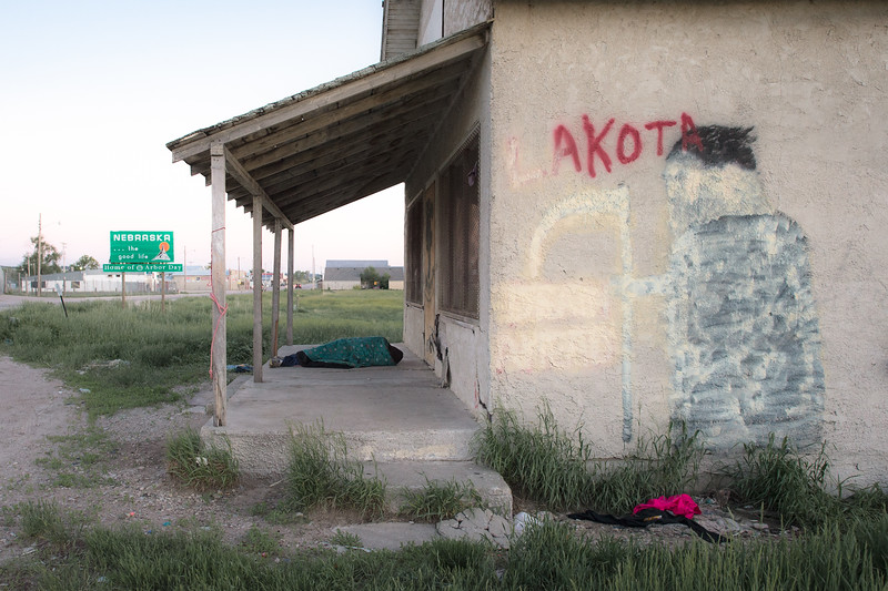 "Painted over graffiti of a grim reaper with the words ""Lakota, Death Ahead.""  Pine Ridge Indian Reservation, SD and Whiteclay, NE border<br /> <br /> Whiteclay was originally part of a 10-mile-wide, 5-mile-deep buffer zone created in 1889 to protect the reservation from whiskey peddlers. President Theodore Roosevelt returned all but one square mile of the land to the public domain in 1904, and alcohol merchants flocked to the area. <br /> <br /> Until 2017, Whiteclay, Nebraska had the highest per capita alcohol sales in the U.S. The village has only 10 residents. Yet its four beer-selling stores sold about 4,500,000 cans per year. That's over 1,200 12-ounce cans per resident per day. Beer sales equaled over a quarter million dollars per resident per year. And some years much more beer was sold. This income and profit was made possible by the self-imposed alcohol prohibition at the large Pine Ridge Indian Reservation.<br /> <br /> The ""Skid Row of the Plains"" is now a dry town."
