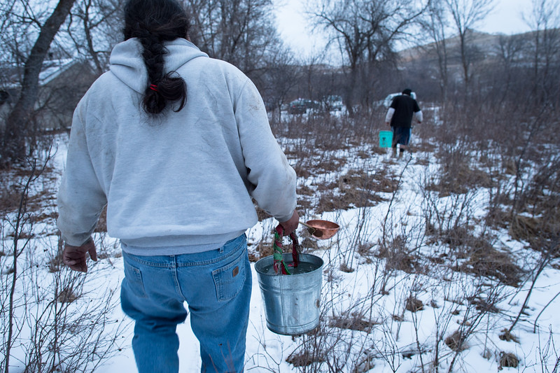 Two Lakota men return from collecting water from a nearby stream in preparation for the second sacred Lakota rite, the Inipi; the rite of purification.