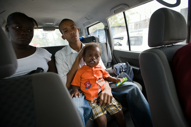 Parents of a child with an unusual bi-lateral cleft make their way to the Baptist Mission Hospital in Fermathe, Haiti. A team of surgeons and nurses from Surgical Volunteers International led Smile Train's first initiative to Haiti in 2009.