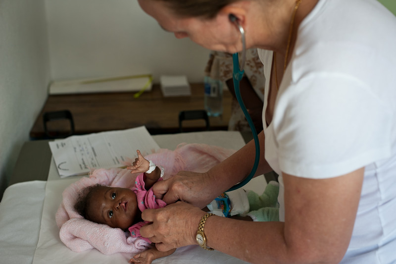 Haiti. An anesthesiologist re-checks the lung fields of a baby with a common cold. Due to the baby's age and weight, it was decided to reschedule the surgery for another time.