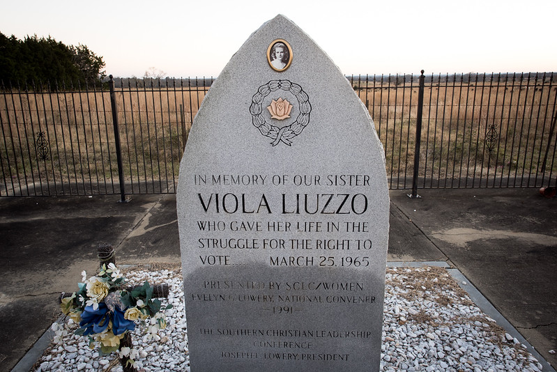 Lowndesboro, AL. 12/7/2015. On March 25, 1965, Viola Liuzzo and Leroy Moton, a 19-year-old local black activist, headed to Montgomery, Alabama to pick up the last group of demonstrators waiting to return to Selma. At 7:37pm, while stopped at a traffic light in front of the Edmund Pettus Bridge in Selma, they were spotted by four Klansmen, who were, according to the testimony from one of the Klansmen, had spent the day seeking an opportunity to kill Martin Luther King.<br /> <br /> When they saw Liuzzo, who was white, driving a car with Michigan plates after dark with a black man in her passenger seat, they decided to attack them instead. The Klansmen hoped that this would send a clear message about white supremacy to northern whites, southern blacks, and like-minded liberals. Engaging Liuzzo in a high-speed chase on Highway 80, they pulled alongside her car about 20 miles outside of Selma and fired. Liuzzo was killed instantly and Moton, covered in her blood, escaped by pretending to be dead.<br /> <br /> The discoloration on the lower portion of the memorial marker is the result of repeated vandalism – one time in particular, a large Confederate flag was painted across the face of the stone in 1997.