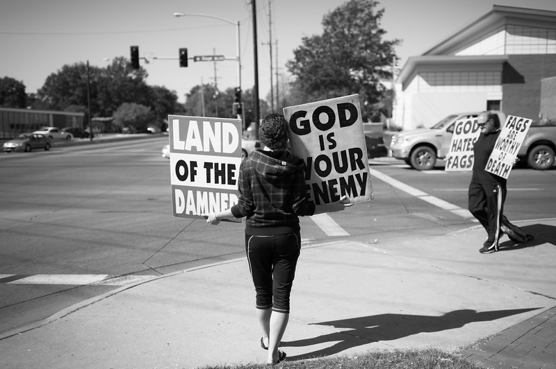 "Former member Megan Phelps-Roper, at the time of this photo was a 25-year-old law office secretary and logistics coordinator for the Westboro Baptist Church, picketing on Gage Road in Topeka, KS. Gage Park was known to some as a ""cruising"" or meet up location in the gay community back in the late 80's, early 90's. The first protest was held blocks from the Phelps home in June 1991 when, according to Pastor Phelps, a homosexual tried to lure his then five-year old grandson into some shrubbery. The location of the incident was Gage Park, a known meeting place for homosexual activity. The family still protests at this location on a daily basis."