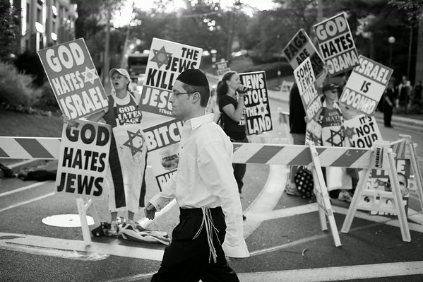 Members of the Westboro Baptist Church hold a picket against Jews in the largely Jewish community of Great Neck, NY. They acknowledge needing the press in order to complete their task of effectively preaching the word of the Lord. Some of the signs displayed that day stated that the Jews killed Jesus and Israel has stolen land from the Palestinians.