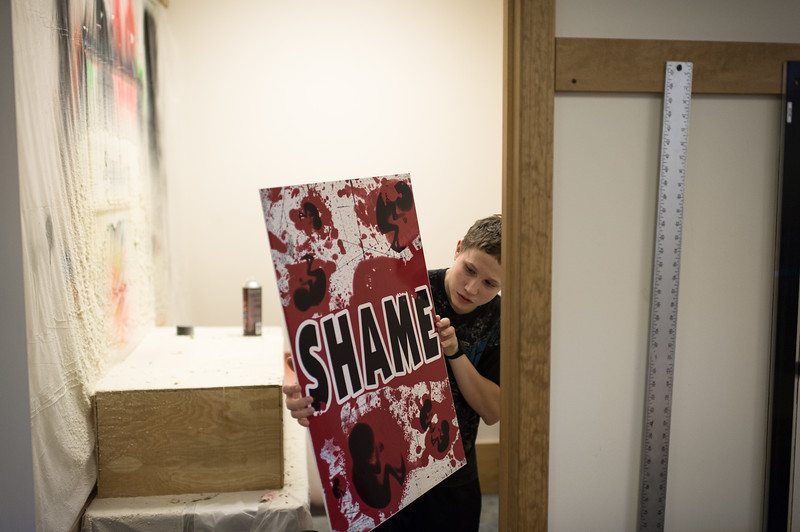 "Jonah Phelps-Roper prepares a picket sign in the ""spray room."" The room is part of the sign shop, which is a highly efficient production facility within the Westboro compound."