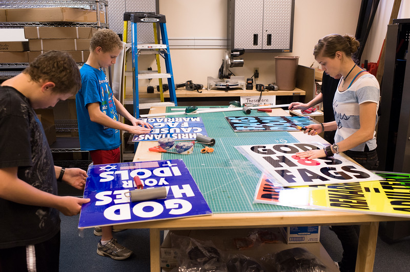 Family members in the sign shop preparing signs for an upcoming protest. The Westboro Baptist Church is based in a circle of houses in a middle-class Topeka neighborhood. In one house, Phelps raised his family, and eventually the neighbors' houses were purchased, effectively creating a compound. All the houses share a large fenced backyard, which includes a full-sized pool and basketball court.