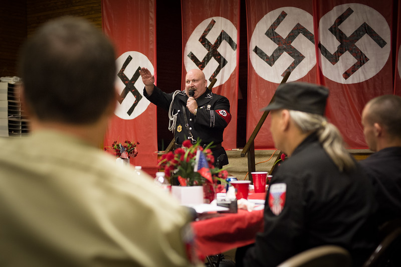 "Former professional wrestler Duke Schneider, a.k.a. ""Pitbull,"" attempts to energize his comrades with a Sieg Heil salute. <br /> <br /> In 2013 Mr. Schneider resigned from the National Socialist Movement and married Katherine Boone, a black woman and former TV personality."