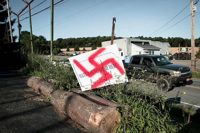 "7/17/2020. A pickup truck drives past the home of a devout white nationalist.<br /> <br /> Following an interview that misrepresented a town as a ""hotbed of white supremacy in 2018, frustrated residents plastered the county with more than 150 signs reading, ""Hate Has No Home Here. Love Wins!!!"""