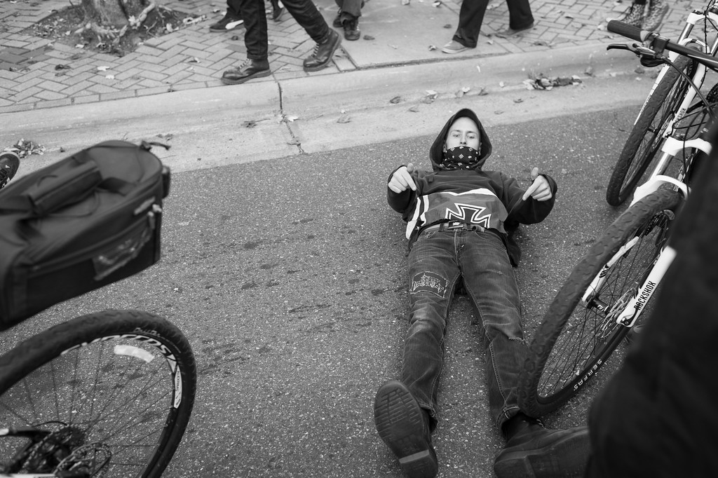A counter protester lies down in the path of a police escorted march of the NSM (National Socialist Movement) as he directs attention to a destroyed Nazi themed flag tucked in his pants. Charlotte, North Carolina.
