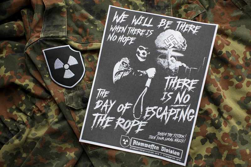 A German Flecktarn field jacket and propaganda flyer belonging to a former member of the Atomwaffen Division.