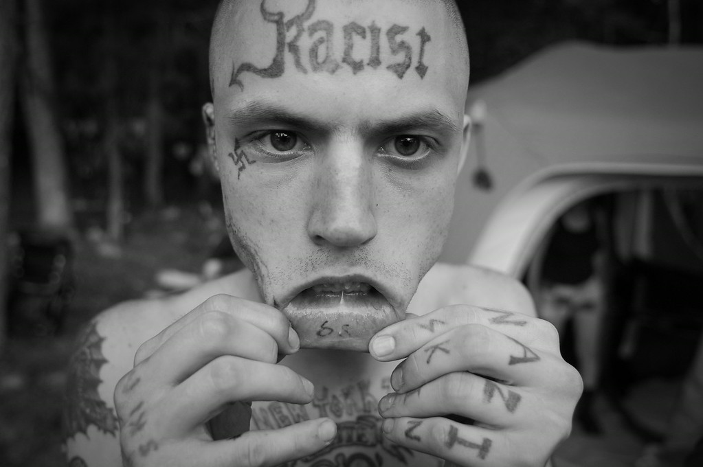 """""""Hachet"""" displays his skinhead tattoos."""
