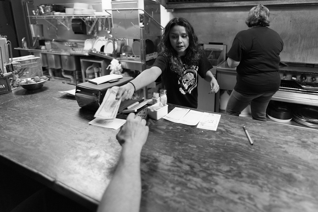 April 23, 2016. Temple, Georgia. A manager at the bar hosting a pro-white solidarity and united front meeting serves a customer wearing an Schutzstaffel unit/SS logo t-shirt.