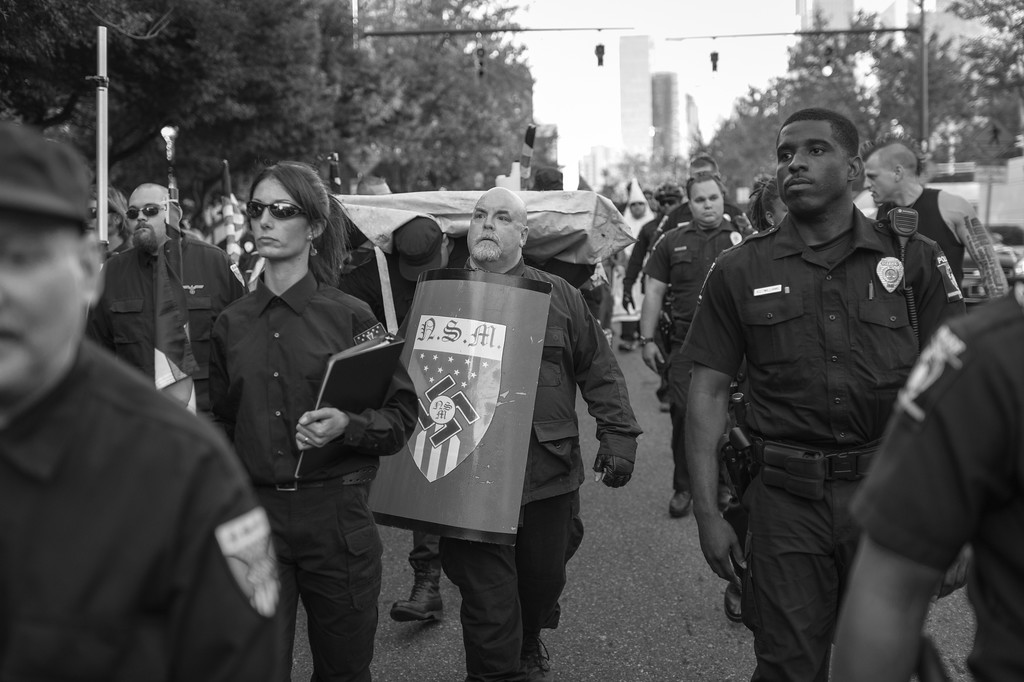 Members of the NSM (National Socialist Movement) and a North Carolina based Ku Klux Klan realm are escorted back to their vehicles by the Charlotte Police department following a rally at the Old City Hall in Charlotte, North Carolina. The rally was held in protest of America's loose policies towards undocumented immigrants. <br /> <br /> The nationalist holding the shield is a mole, a member of the antifata who used his ties within the music scene to infiltrate the organization.
