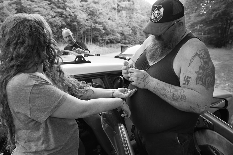 A carload of skinheads pull over for some impromptu roadside shooting. Here, the president of the organization loads .380-caliber ammunition into a clip for his wife