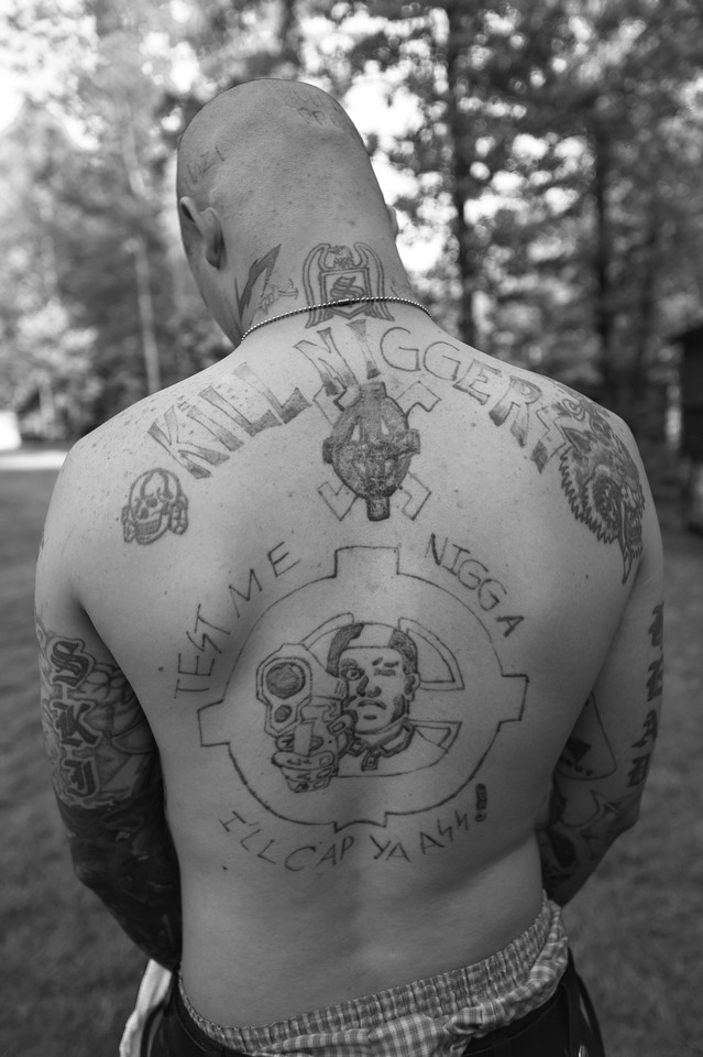 A member of the Supreme White Alliance displays his skinhead tattoos.