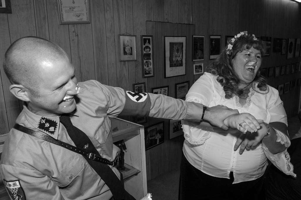 "Christine and Steven celebrate at their wedding having cut their cake with blue icing at the annual ""Nationals"" weekend of the National Socialist Movement (NSM) in Laurens, S.C. on April 21, 2007. The wedding was performed in Nazi tradition with a text borrowed in part from an original 3rd Reich Era SS style wedding ceremony that was pulled from the archives by one of NSM's Party Historians. NSM Commander Jeff Schoep (not pictured) officiated."