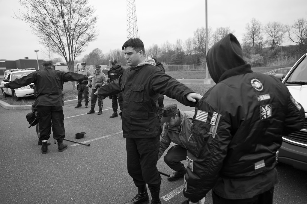 NSM (National Socialist Movement) members in the process of being searched by state police prior to a demonstration in Trenton, NJ.