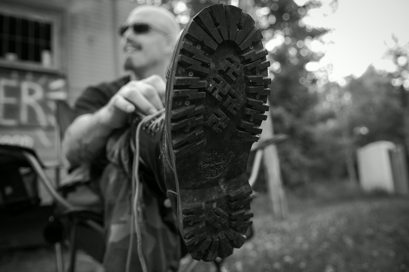 A member of the Imperial Klans of America laces up a new pair of Aryan Wear panzer boots at their annual Spring Festival. Dawson Springs, Kentucky.