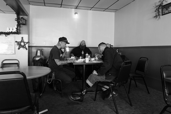 Several skinheads having a late breakfast at the culmination of a weekend get together.