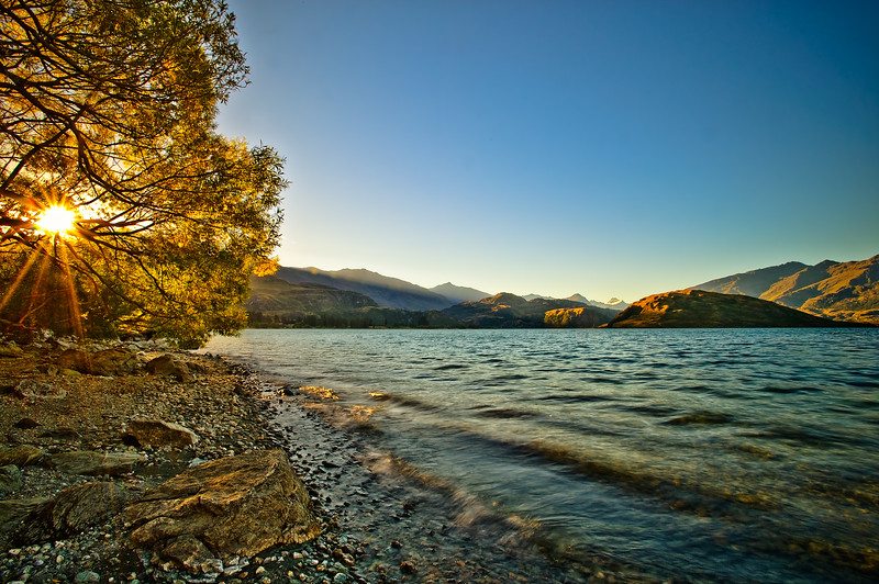 Sunset at Glendhu Bay<br /> Holidaymakers to Central Otago always have fond memories of this bay. Mt Aspiring is illuminated in the distance as the calm of Lake Wanaka promises a time of barbecues, charcoal, fish, beer and relaxation.