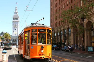 Historic streetcar on San Francisco's Market St. The vibrant orange contrasts well with the white Ferry Building.  ヒストリック・ストリートカーと呼ばれるサンフランシスコの路面電車。ビビッドなオレンジ色が白のフェリー・ビルディングに映える。