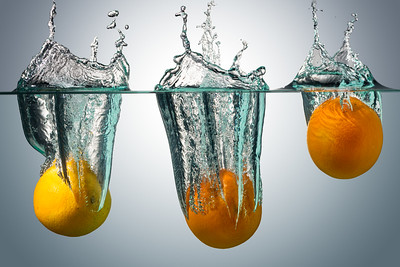 Oranges falling into water on gradient blue background