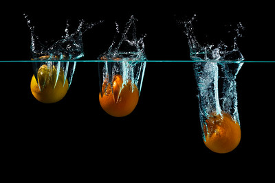 Oranges falling into water with black background