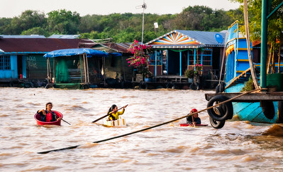 "Two Girls and a Puppy playing in makeshift boats between houses of the ""Floating Village"" - Siem Reap River, Cambodia"