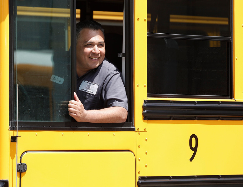 Vehicle maintenance technician, Andrei Rayas, named 2017 Classified School Employee of the Year in the Transportation category, looks on as his co-workers joke with him as he parks a bus at North Monterey County Unified School District's maintenance and transportation yard on Tuesday, April 25, 2017 in , Calif. (Vernon McKnight/Herald Correspondent)