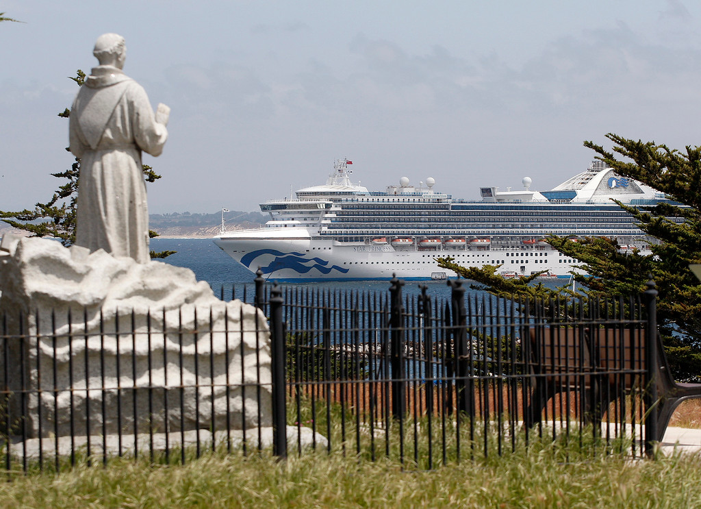 . The Junipero Serra statue at the Lower Presidio Historic Park looks over the Princess Cruises Star Princess cruise ship at anchor off Monterey on Monday, April 30, 2018.  (Vern Fisher - Monterey Herald)