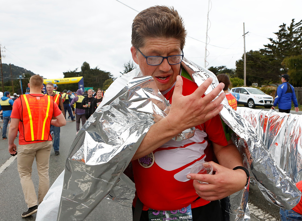 . Axel Schier throws on a heat sheet after finishing the Big Sur Marathon in Carmel, Calif. on Sunday April 29, 2018. (David Royal/ Herald Correspondent)