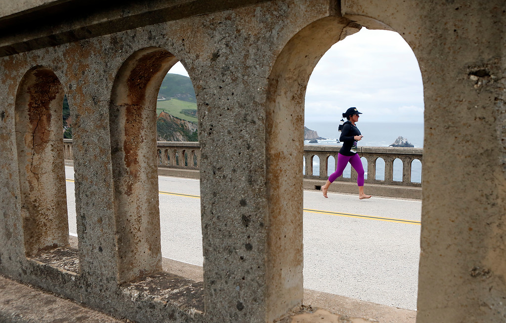 . A barefoot woman crosses Bixby Bridge during the Big Sur Marathon in Big Sur, Calif. on Sunday April 29, 2018. (David Royal/ Herald Correspondent)