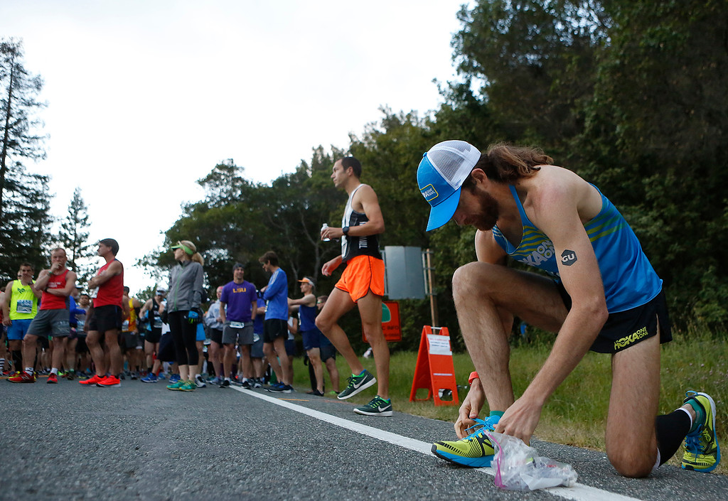 . Former winner Michael Wardian ties his shoes as 2018 winner Adam Roach warms up behind before the start of the Big Sur Marathon in Big Sur, Calif. on Sunday April 29, 2018.Roach won the race, Wardian placed third. (David Royal/ Herald Correspondent)
