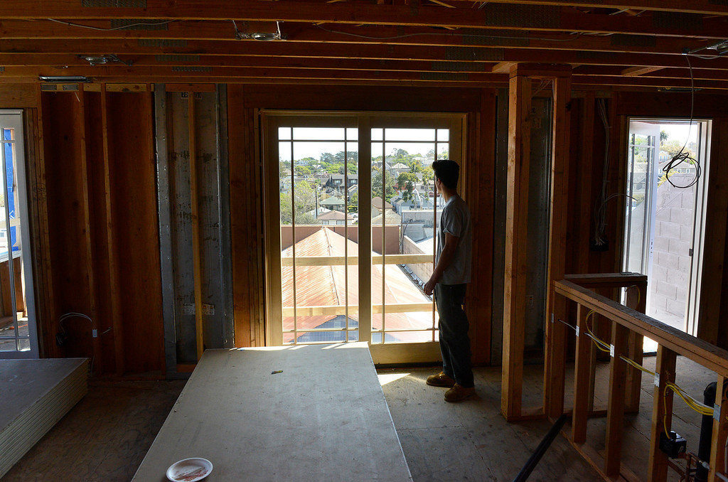 . Kane Miller looks out over roof tops and across the bay from a window on the third floor of a new mixed use building his father\'s company is developing on Grand Avenue in downtown Pacific Grove on Monday April 10, 2017. The building will have apartments on the top two floors and a commercial space downstairs. (David Royal - Monterey Herald)