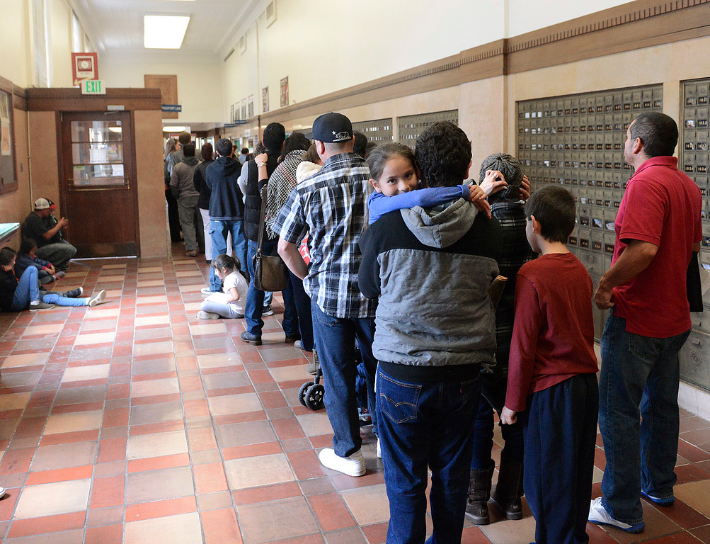 . Alexa Gonzales sits in her brother Carlos\' arms while waiting in a long passport line at the Stenbeck Post Office on West Alisal in Salinas on Thursday April 13, 2017. (David Royal - Monterey Herald)