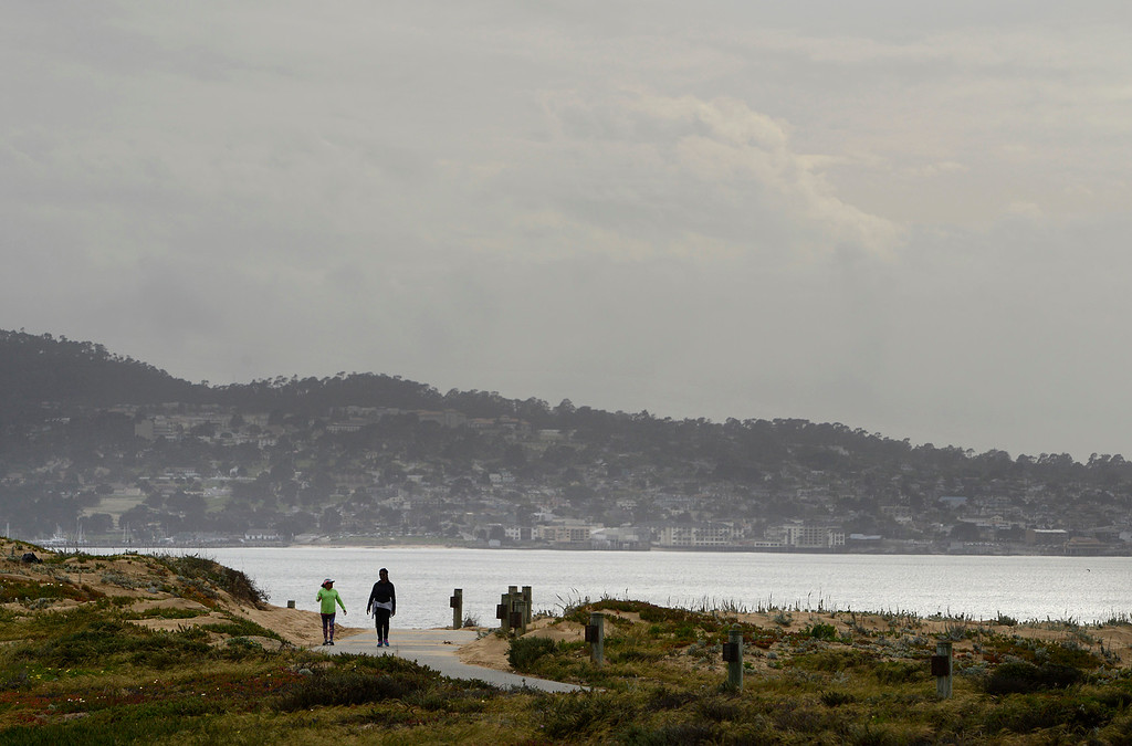 . Women walk the Recreation Trail in Sand City as clouds loom over the Monterey Peninsula on on Friday April 7, 2017. (David Royal - Monterey Herald)
