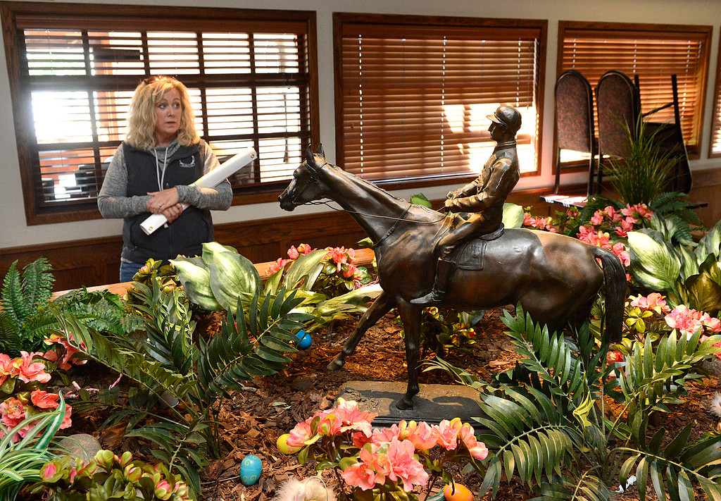 . Monterey County Fair and Events Center CEO Kelly Violini stands behind a statue of a jockey riding a racing horse inside Monterey Bay Race Place off-track betting venue at the Monterey County Fair and Events Center in Monterey on Monday April 10, 2017. The facility is housed in the former Turf Club. (David Royal - Monterey Herald)