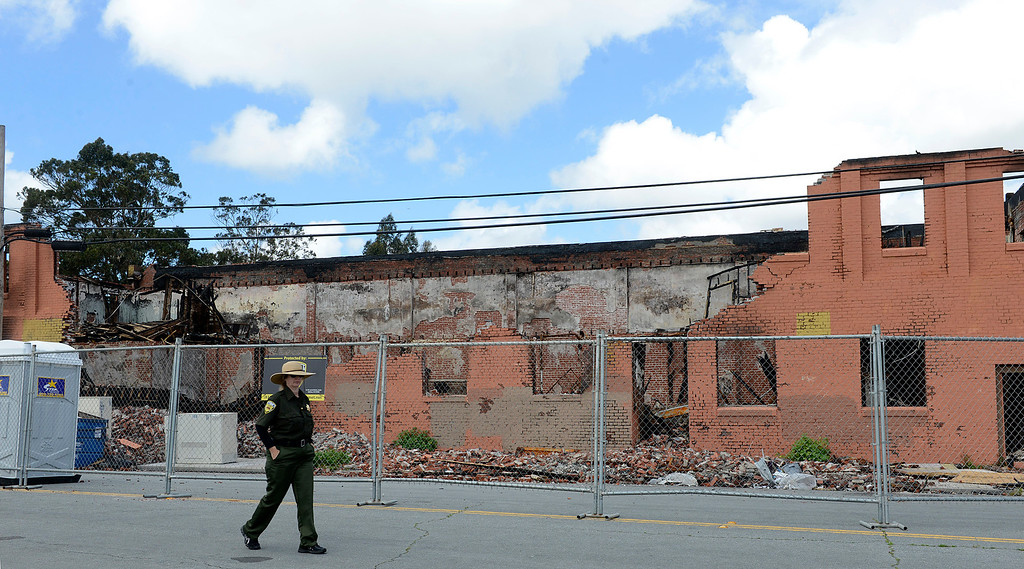 . A security guard walks past the fire-gutted brick Swinging Door building in the Chinatown area of lower Soledad Street on April 13, 2017. The Salinas Fire Department announced that the blaze in the vacant building on March 18, 2017 was likely caused accidentally by a homeless man trying to create a makeshift cooking pit. (David Royal - Monterey Herald)