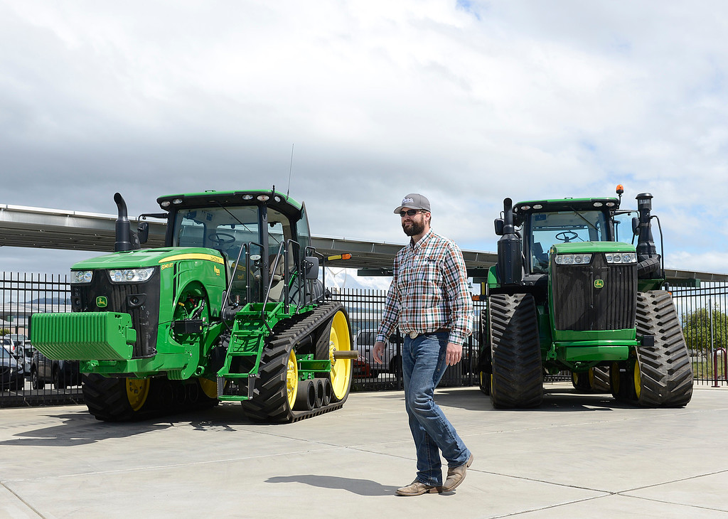 . Adam Jacop of RDO Equipment of Salinas walks past the John Deere 8345 RT two track, and the John Deere 9470RX four track tillage tractors that his company offers during the Ag Tech Summit at Hartnell College Agriculture Business & Technology Institute in Salinas on Wednesday April 12, 2017. (David Royal - Monterey Herald)