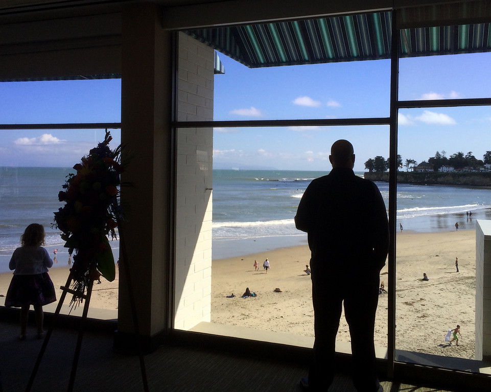 . A young girl and man look out from a memorial for surfer Matt Hamil in the Dream Inn toward waves rolling in at Cowell\'s Beach in Santa Cruz on Saturday April 8, 2017. (David Royal - Monterey Herald)