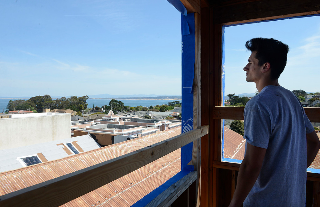 . Kane Miller looks out over roof tops and across the bay from a balcony on the third floor of a new mixed use building his father\'s company is developing on Grand Avenue in downtown Pacific Grove on Monday April 10, 2017. The building will have apartments on the top two floors and a commercial space downstairs. (David Royal - Monterey Herald)